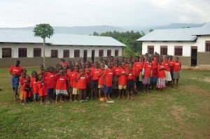 Standing in front of their new school, completed Feb 2014, the children sing Thank You songs of Love.