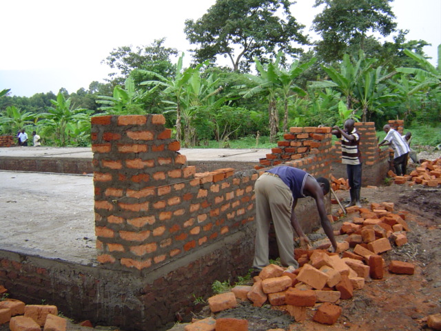 After the concrete floor was left to settle for a few days (..thank you to the rain that fell intermittently and assisted in the process) brick work began on all four corners of each building