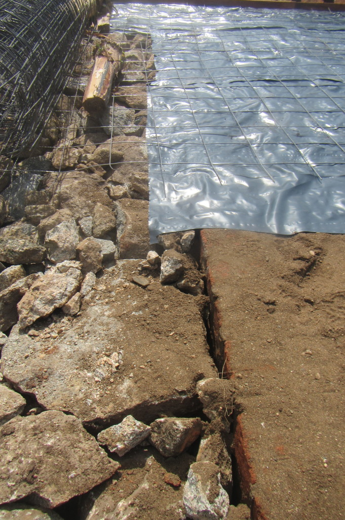 This picture shows a few layers of the floor process.. on the left the hardcore, on the upper right, the polythene paper and metal reinforcement, on the lower right, the pounded aggregates and sand followed by a final layer of sand..